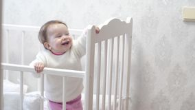 De baby speelt en glimlacht in babybed stock footage
