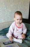 De baby speelt met een smartphone Stock Afbeeldingen