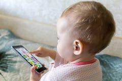 De baby speelt met een smartphone Stock Afbeelding