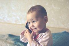 De baby speelt met een smartphone Stock Foto