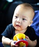 De baby speelt met een stuk speelgoed royalty-vrije stock foto