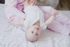 De baby speelt op haar moeder` s overlapping stock foto
