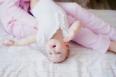 De baby speelt op haar moeder` s overlapping in de slaapkamer stock fotografie