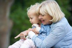 De baby van de grootmoederholding meisje en het richten Stock Afbeelding