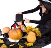 De baby van Halloween met moeder die dichtbij pumpking Royalty-vrije Stock Foto's