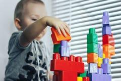 De baby van het babyspel constructorLittle het spelen met veel kleurrijk plastiek blokkeert aannemer dichtbij venster Royalty-vrije Stock Foto