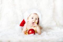 De baby van Kerstmis in rode hoed die op bont ligt Royalty-vrije Stock Foto's