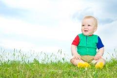 De baby van Liitle zit op gras Royalty-vrije Stock Fotografie