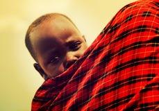 De baby van Maasai die door zijn moeder in Tanzania, Afrika wordt vervoerd Stock Afbeeldingen