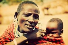 De baby van Maasai die door zijn moeder in Tanzania, Afrika wordt vervoerd Stock Foto