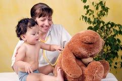 De baby van Playrful bij de arts. Stock Foto