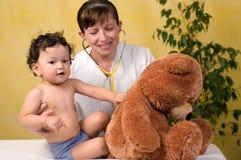 De baby van Playrful bij de arts. Stock Afbeelding