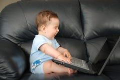 De baby van Smilling met laptop op een bank Stock Foto