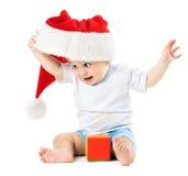 De baby verwijdert zijn santahoed Stock Afbeelding