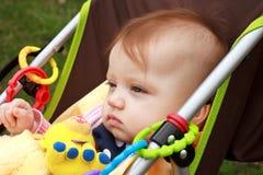 De baby in Wandelwagen staart Stock Foto's