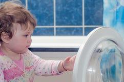 De baby zet linnen in wasmachine Stock Foto's