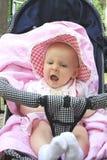 De baby zit in een vervoer met een open mond royalty-vrije stock afbeeldingen