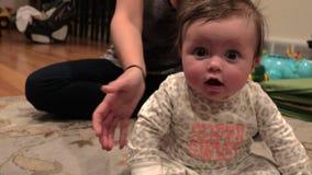 De baby zit omhoog, maar valt om stock footage