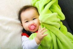 De baby zuigt met fopspeen stock afbeelding