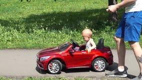 De babyjongen berijdt een stuk speelgoed auto door vader wordt gedreven die stock video