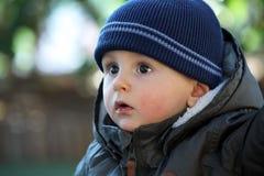 De babyjongen die een Blauw dragen breit de Winterhoed en Groene de Winterparka stock foto's