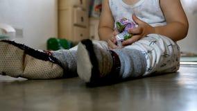 De babyjongen die van de close-upmening op vloer situeren thuis en met plastic pak zakweefsels spelen stock foto's