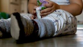 De babyjongen die van de close-upmening op vloer situeren thuis en met plastic pak zakweefsels spelen royalty-vrije stock afbeelding