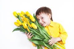 De babyjongen drie jaar in een geel overhemd ligt op een witte backgroun Stock Afbeelding