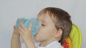 De babyjongen drinkt water van een fles stock footage