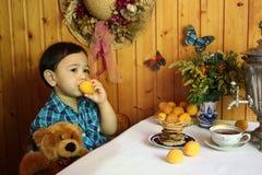 De babyjongen eet abrikoos in de keuken van het land Stock Fotografie