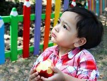 De babyjongen eet appel op een kinderenspeelplaats Royalty-vrije Stock Foto