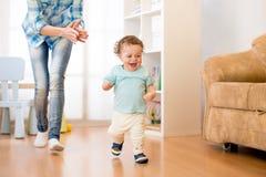 De babyjongen heeft een pret die in woonkamer met zijn moeder lopen stock fotografie