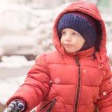 De babyjongen kijkt naar terwijl het sneeuwen Royalty-vrije Stock Fotografie
