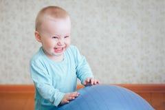 De babyjongen lacht met grote bal Stock Foto