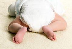De babyjongen ligt met luiers royalty-vrije stock foto
