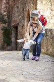 De babyjongen maakt zijn eerste stappen met zijn moeder Stock Afbeeldingen