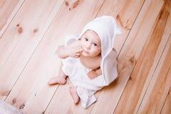 De babyjongen met bruine ogen is vijf die maanden oud in een witte handdoek met oren op houten achtergrond worden verpakt Royalty-vrije Stock Foto's