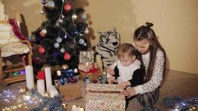 De babyjongen met zuster pakt de doos van de Nieuwjaar` s gift dichtbij een prachtig verfraaide Kerstboom uit stock video
