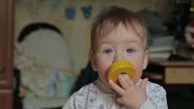De babyjongen neemt in haar mond helder stuk speelgoed stock footage