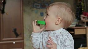 De babyjongen neemt in haar mond helder stuk speelgoed stock video