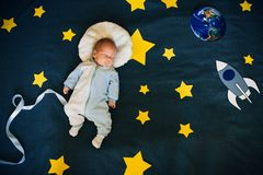 De babyjongen is in slaap en droomt zich een astronaut in ruimte stock afbeeldingen