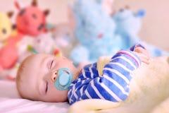 De babyjongen slaapt naast zijn gevuld speelgoed stock afbeelding