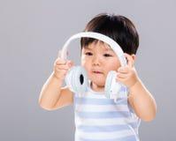 De babyjongen wil luisteren muziek gebruikend hoofdtelefoon Stock Foto's
