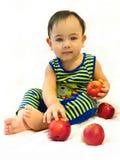 De babyjongen zit met rode appelen Stock Fotografie