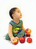 De babyjongen zit met rode appelen Royalty-vrije Stock Afbeelding