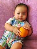 De babyjongen zit op een roze handdoek met sinaasappel Royalty-vrije Stock Afbeeldingen