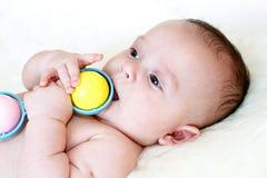 De babyleeftijd van 3.5 maanden speelt een rammelaar stock foto
