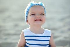 De babymeisje van Ð ¡ Ute in aardige gestreepte kleding en blauwe hoofdband die en haar eerste tanden glimlachen tonen stock afbeeldingen