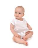De babymeisje van het zuigelingskind in luierzitting en het gelukkige bekijken Th Royalty-vrije Stock Fotografie