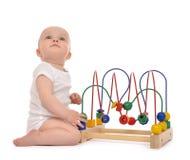 De babypeuter die van het zuigelingskind en houten educationa bevinden zich spelen Royalty-vrije Stock Afbeeldingen